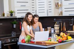 Two twin sisters looking for salad recipe on the Internet Stock Images