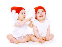 Two twins baby in hats playing Stock Photos