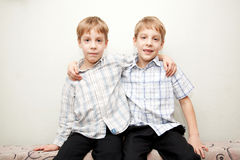 Two twins brothers hugging and smiling. Two twins brothers wearing checkered shirt hugging and smiling stock photos