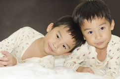 Two twins brothers. Lying on bed Royalty Free Stock Photo