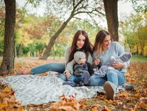 Two twins girls, are sitting in an autumn park with a little boy and baby. Two young and beautiful twins girls, European-looking, with dark long hair, are Royalty Free Stock Photography