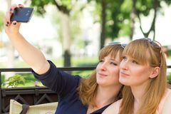 Two twins girls taking selfie in restaurant. Royalty Free Stock Photography