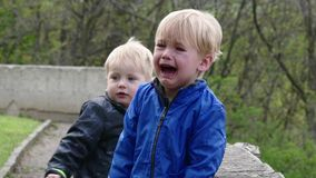Two twins, one of them crying loudly. Outdoors stock footage