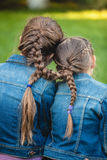 Two twins with tied long braids Stock Photography