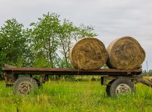 Two twisted hay rolls on a cart in the field stock photos