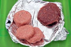 Two types of burger, traditional beefburgers and unusual zebra b. Urgers, on tin foil waiting to be cooked on the barbecue Royalty Free Stock Photos