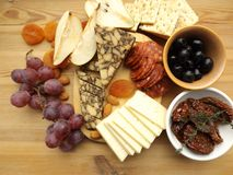 Cheese plate with fruit, snacks. Two types of cheese, chorizo sausage and olives Royalty Free Stock Photography