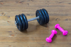 Two types of dumbbells on the floor training room. Two pairs of sports dumbbell in the gym on the floor of the photo on the calendar Stock Image