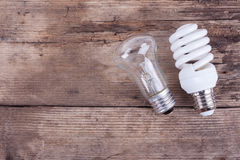 Two types of light bulbs on wooden background Stock Image