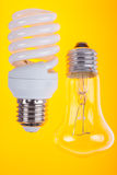 Two types of light bulbs on yellow background Stock Image