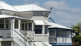 Two styles of Queenslander homes with tin roof and verandahs. Two types of Queenslander homes with stairs , wrap around verandah and tin roof Royalty Free Stock Photos