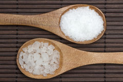 Two types of salt. Wooden spoon with two types salt on bamboo placemat stock image