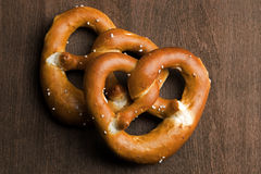 Two typical bavarian pretzel on a brown background Royalty Free Stock Photos