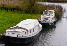Two typical dutch boats docked on the water shore, one covered u royalty free stock photo