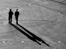 Two Ukrainian policemen, black silhouettes of men from whom stretch long diagonal shadows against background of pavement pavement,. Two Ukrainian policemen Stock Images