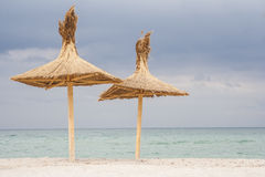 Two Umbrellas on the beach. Two reed umbrellas on a beach in Vama Veche, Romania Royalty Free Stock Photos