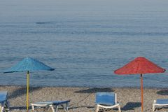 Two umbrellas of red and blue on the background of the sea. Several empty sun loungers are nearby. royalty free stock photos