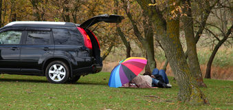 Two under umbrella at grass. Near car in forest Royalty Free Stock Photos