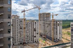Two unfinished multi-storey houses and three building cranes. On the new construction royalty free stock photo