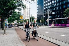 Two unidentified couple riding their bicycles in a street Stock Images