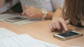 Two unknown students girls with smartphones. Two unidentified female students sit at wooden desk at lesson at the university and thumb their fingers on the stock video footage