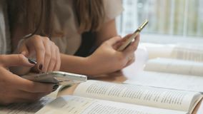 Two unknown students girls with smartphones. Two unidentified female students sit at wooden desk at lesson at the university and thumb their fingers on the stock footage
