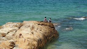 Two unidentified fisherman sitting on a brown rock at the sea. Mui Ne, Vietnam: Two unidentified fisherman sitting on a brown rock at the sea. Scene taken on a stock footage