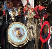 Two unidentified men and woman dress elaborate fancy dresses with gold masks, red and black feather hats during Venice Carnival Stock Images