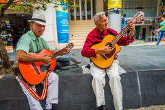 Two unidentify indigenous men playing guitar in Royalty Free Stock Images
