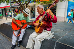 Two unidentify indigenous men playing guitar in Stock Image