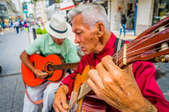 Two unidentify indigenous men playing guitar in Royalty Free Stock Image