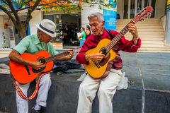 Two unidentify indigenous men playing guitar in Stock Photography