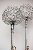 Two unique silver chrome lamps. Two unique shape silver or chrome home design lamps on tall stalks with white background Royalty Free Stock Images