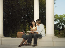 Two university students studying near colonnade, woman with laptop, man holding textbook, smiling royalty free stock images