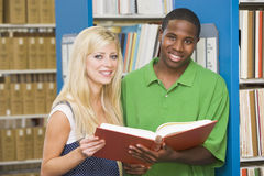 Two university students working in library. Male and female students working in library royalty free stock images