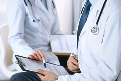Two unknown doctors filling up medical form on clipboard, just hands closeup. Physicians asking question to patient or Royalty Free Stock Images