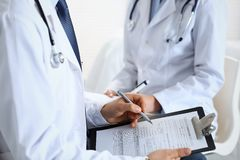 Two unknown doctors filling up medical form on clipboard, just hands closeup. Physicians asking question to patient or. Discussing medication program royalty free stock photos