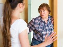 Two unpleased women at doorway Stock Images