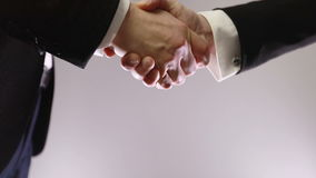 Two unrecognizable business partners shaking hands. Slow motion. Two unrecognizable business partners shaking hands stock footage