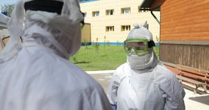 Two unrecognizable doctors or nurses wearing full Ebola virus protection uniform  standing near ambulance car and stock footage