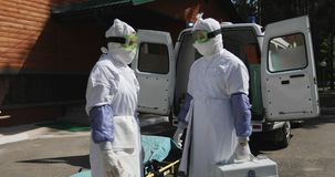 Two unrecognizable doctors or nurses wearing full Ebola virus protection uniform standing near ambulance car and. Two unrecognizable doctors or nurses wearing stock footage