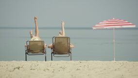 Two unrecognizable young women shaking tanned slim legs on sandy beach. Wide shot back view of Caucasian tourists