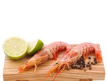 Two untreated royal shrimp a pieces of lime and a pile of black pepper on a board. Isolated. Two untreated big royal shrimp a few pieces of juicy lime and a Royalty Free Stock Photos