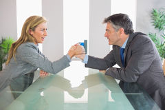 Two upset businesspeople having an arm wrestling sitting around Stock Image