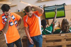 Two upset male football fans in orange t-shirts and their friends in green t-shirts gesturing and celebrating victory during. Watch of soccer match at home royalty free stock image
