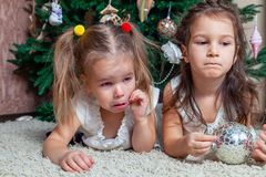 Two upset sisters lying under the holiday tree. One took the Christmas tree toy from the other and she began to cry. Concept of b stock images