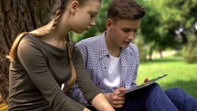 Two upset students searching important information for study on tablet, gadget. Stock photo stock image