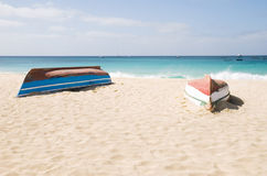 Two upturned boats on beach. Two upturned fishing boats on a stunning sandy beach located in the resort of santa maria in the cape verde islands Stock Photo