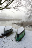 Two upturned boats on winter snow Stock Image