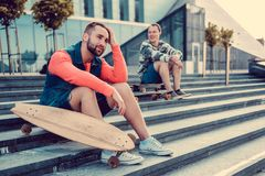 Two urban males posing with longboard. Two urban males posing with longboard on steps in downtown Royalty Free Stock Image